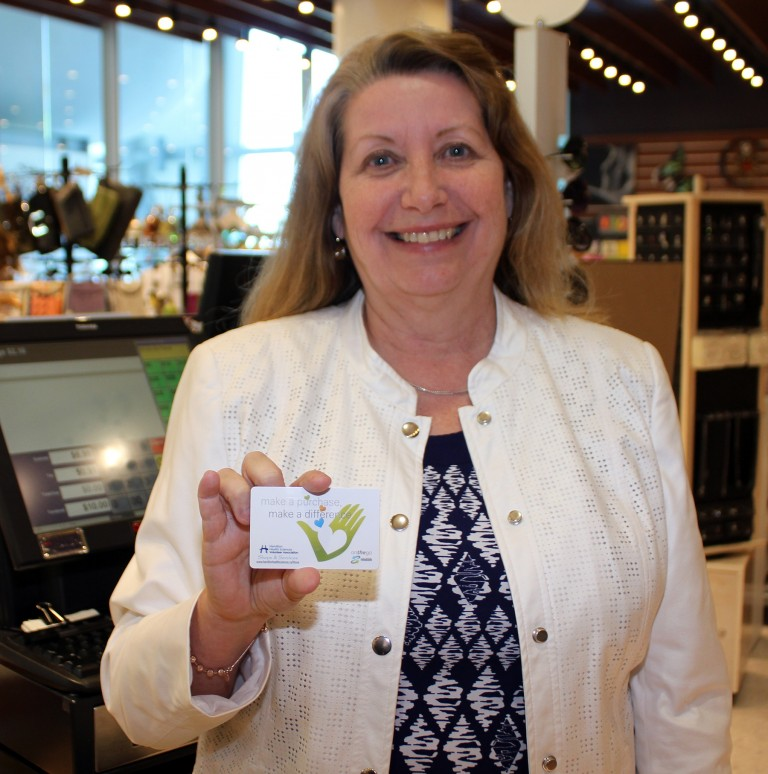 Anne Collins holds up the new OnTheGo gift card offered by HHSVA.